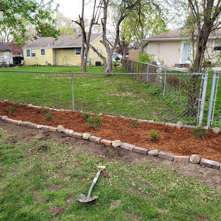 a reviewer photo of the yard now with a mulch-filled flower bed