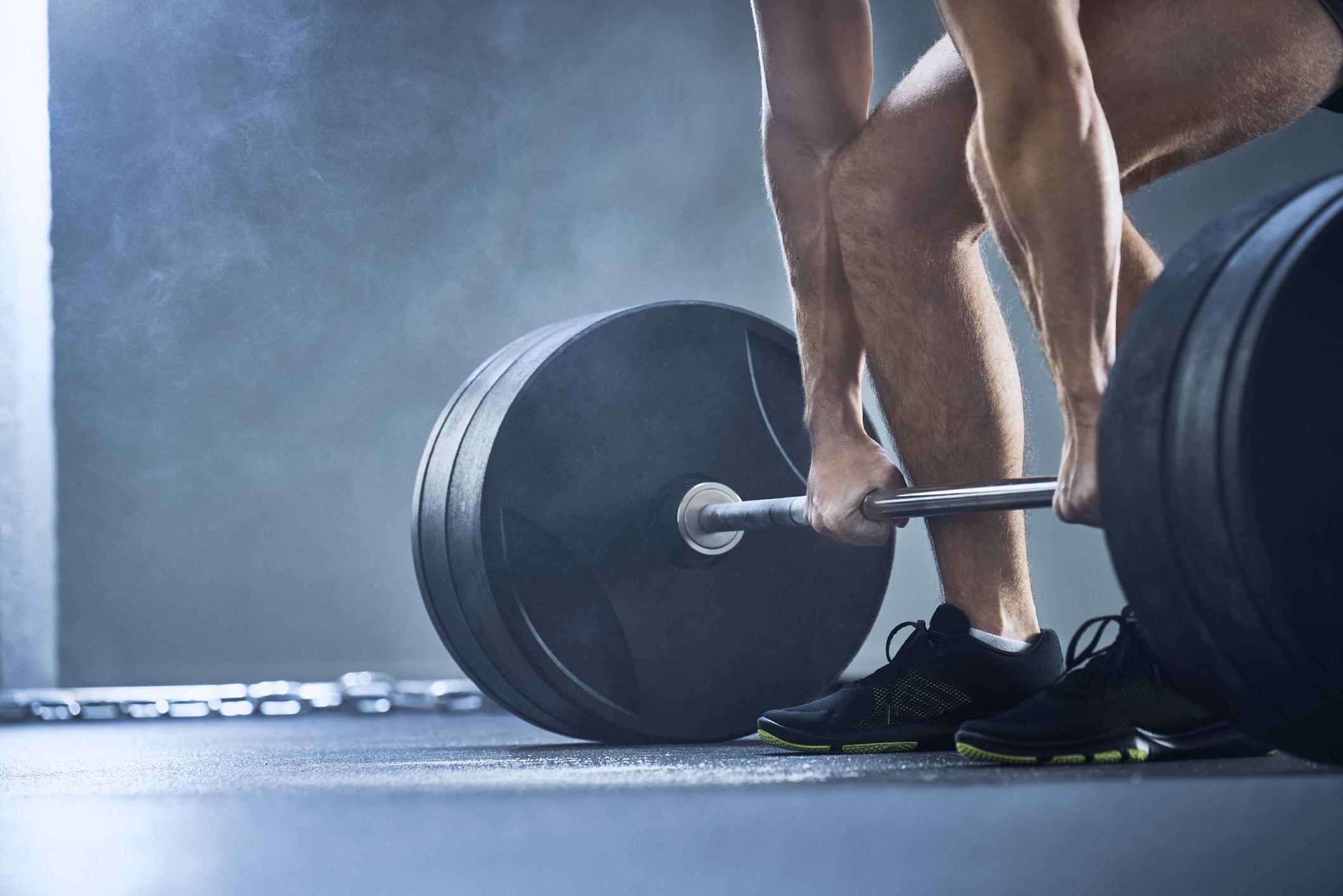 """杠铃和重物在地板上的落地镜头,显示一名男子';他的腿和胳膊,因为他俯身拿起它""""class="""