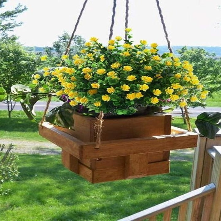 a hanging basket filled with a cluster of fake yellow flowers