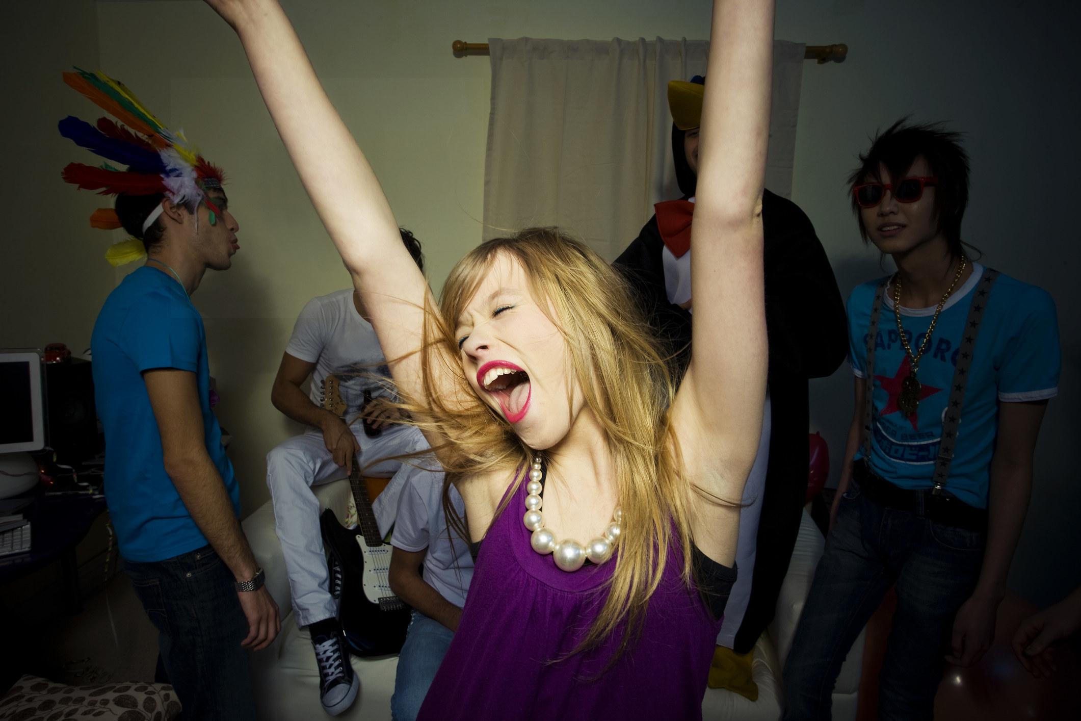"""派对女孩高举双臂高喊着,在一群男人的阴影中""""class="""