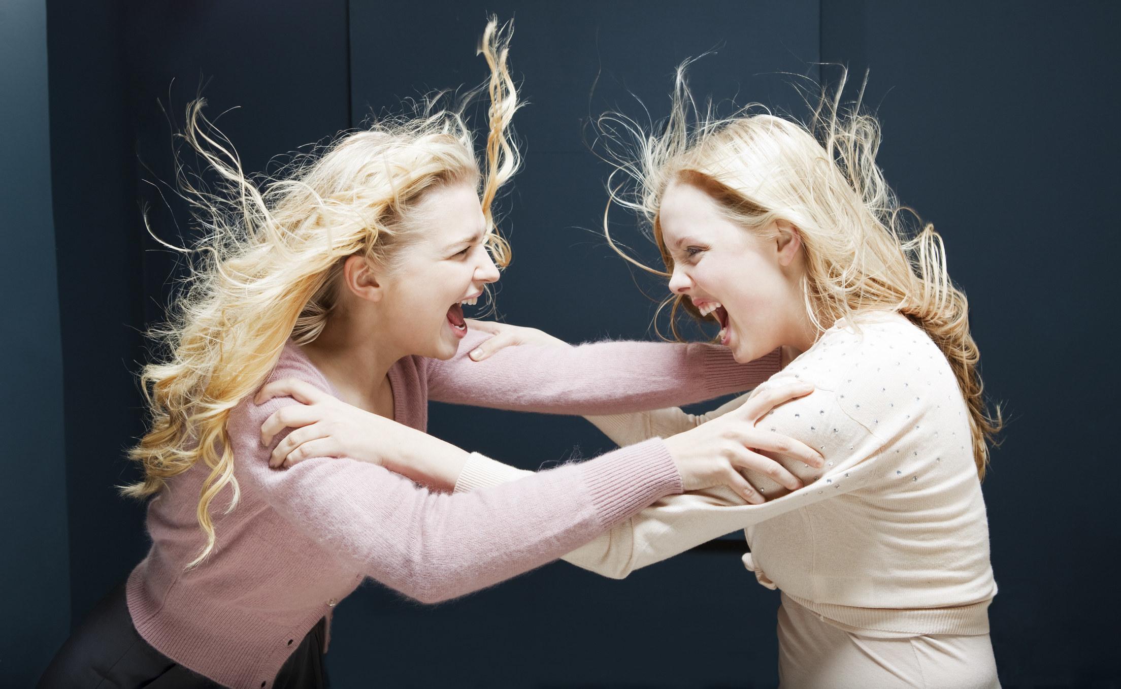 """两个女人用胳膊互相抓着喊叫';她的肩膀,在战斗""""class="""