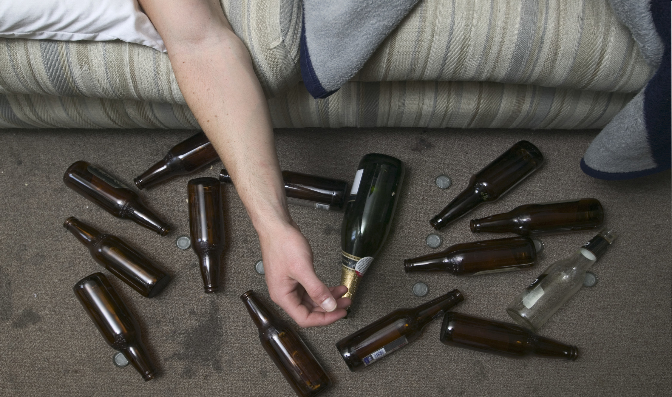 """一只胳膊从沙发上掉下来,趴在地上的一堆空啤酒瓶和瓶盖上""""class="""