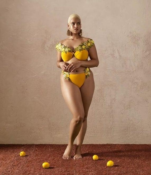 """在黄色比基尼泳装的模型与叶子和柠檬饰物""""class="""