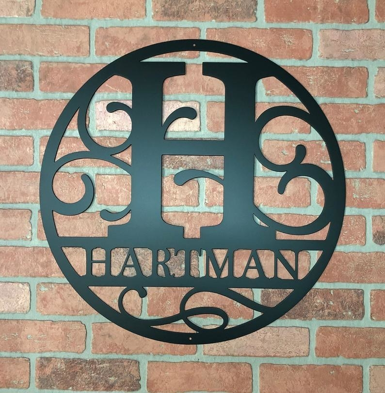 """a steel circle monogram featuring the letter H and the name """"Hartman"""" mounted on a brick wall"""