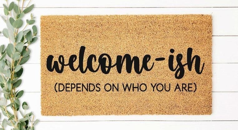 """a tan doormat that says """"welcome-ish (depends on who you are)"""""""