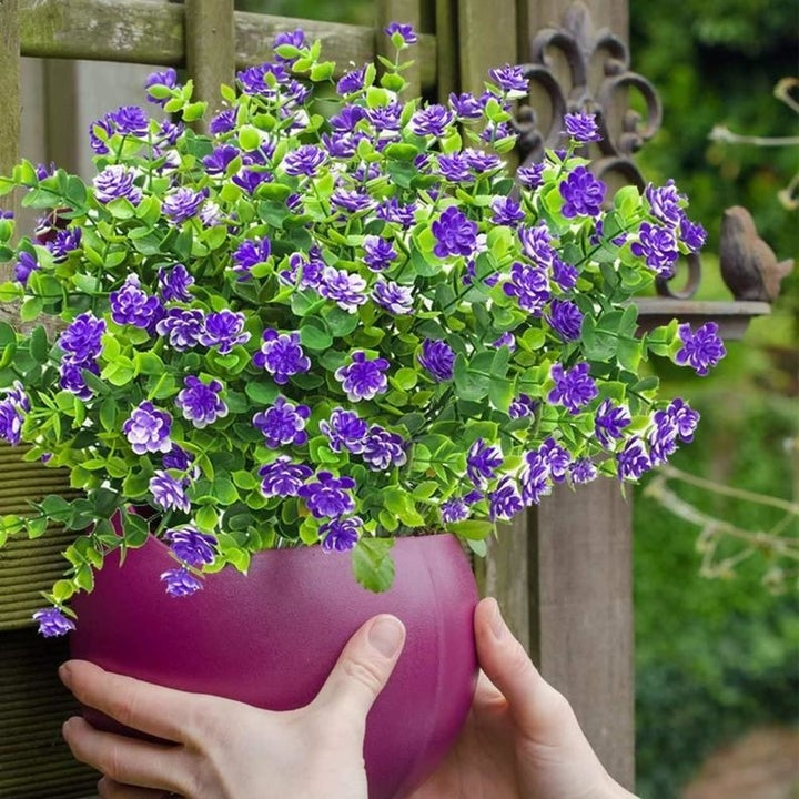 a pair of hand holding a purple planter filled with a bundle of fake purple flowers