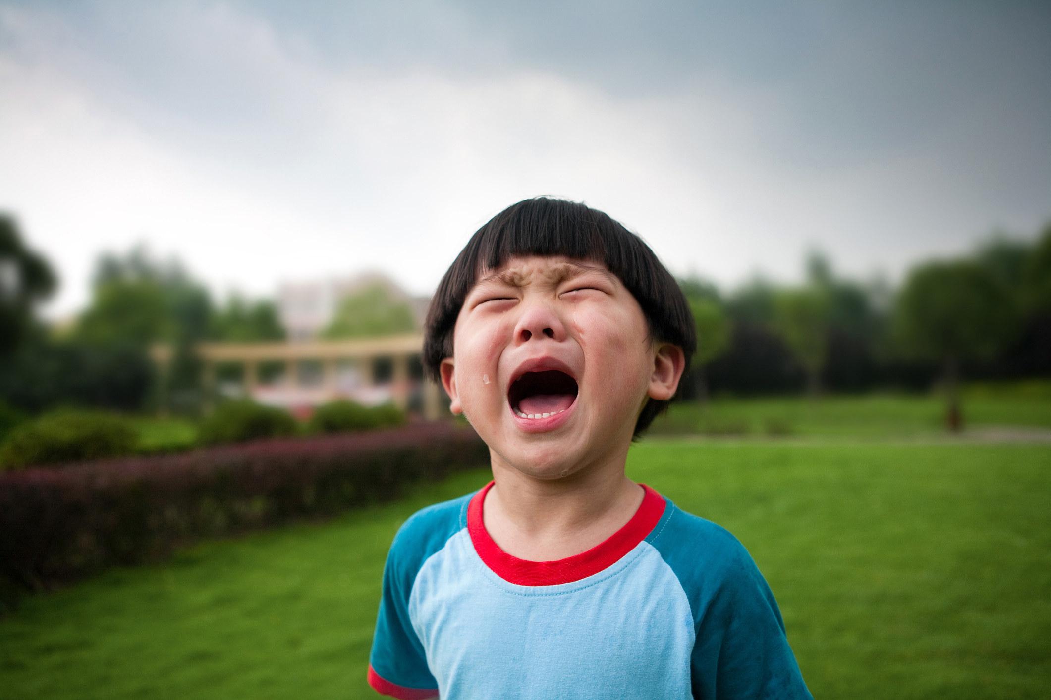 """一个小男孩在外面的院子里闭着眼睛,张着嘴哭着,眼泪在脸颊上""""class="""