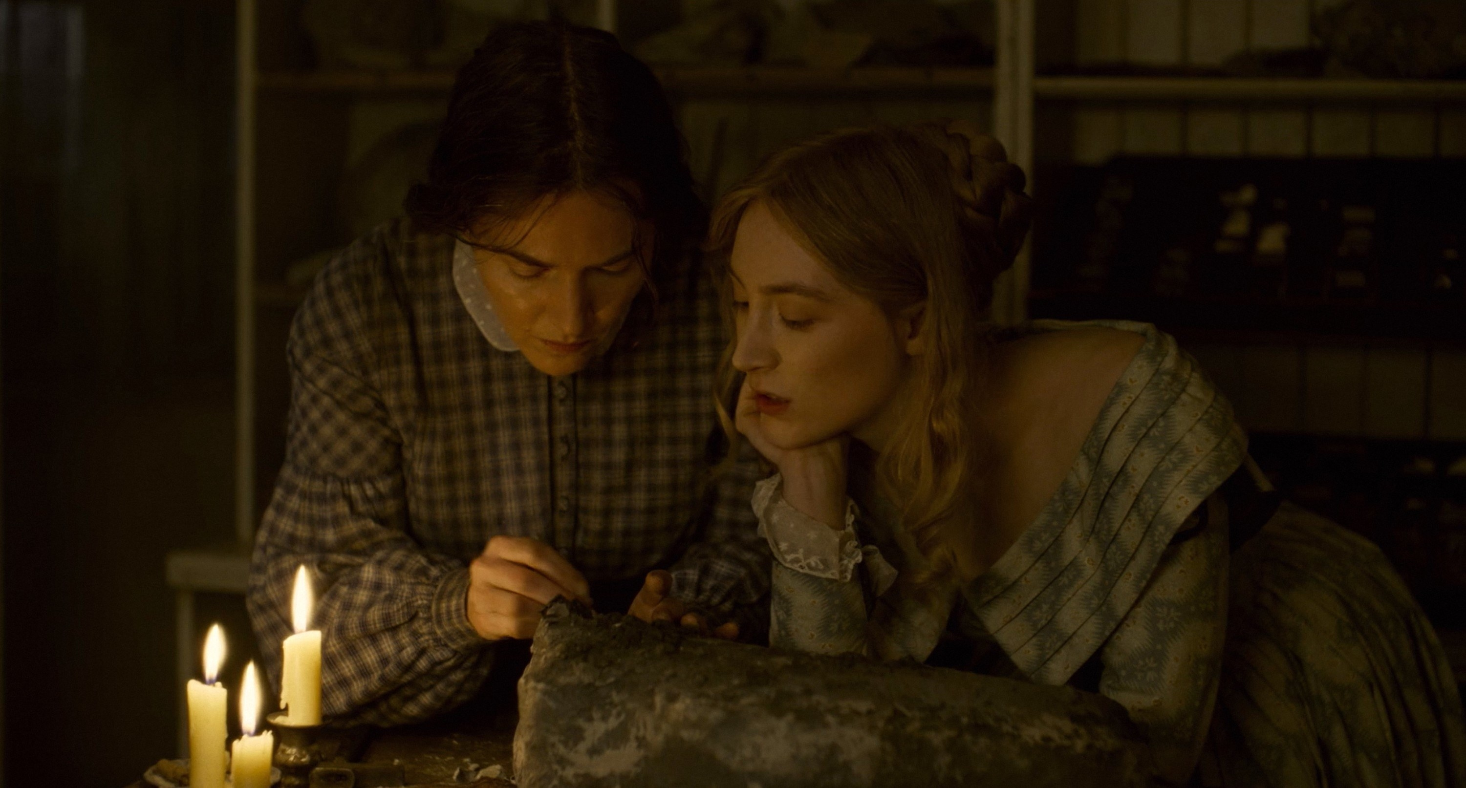 Kate Winslet and Saoirse Ronan looking at a fossil