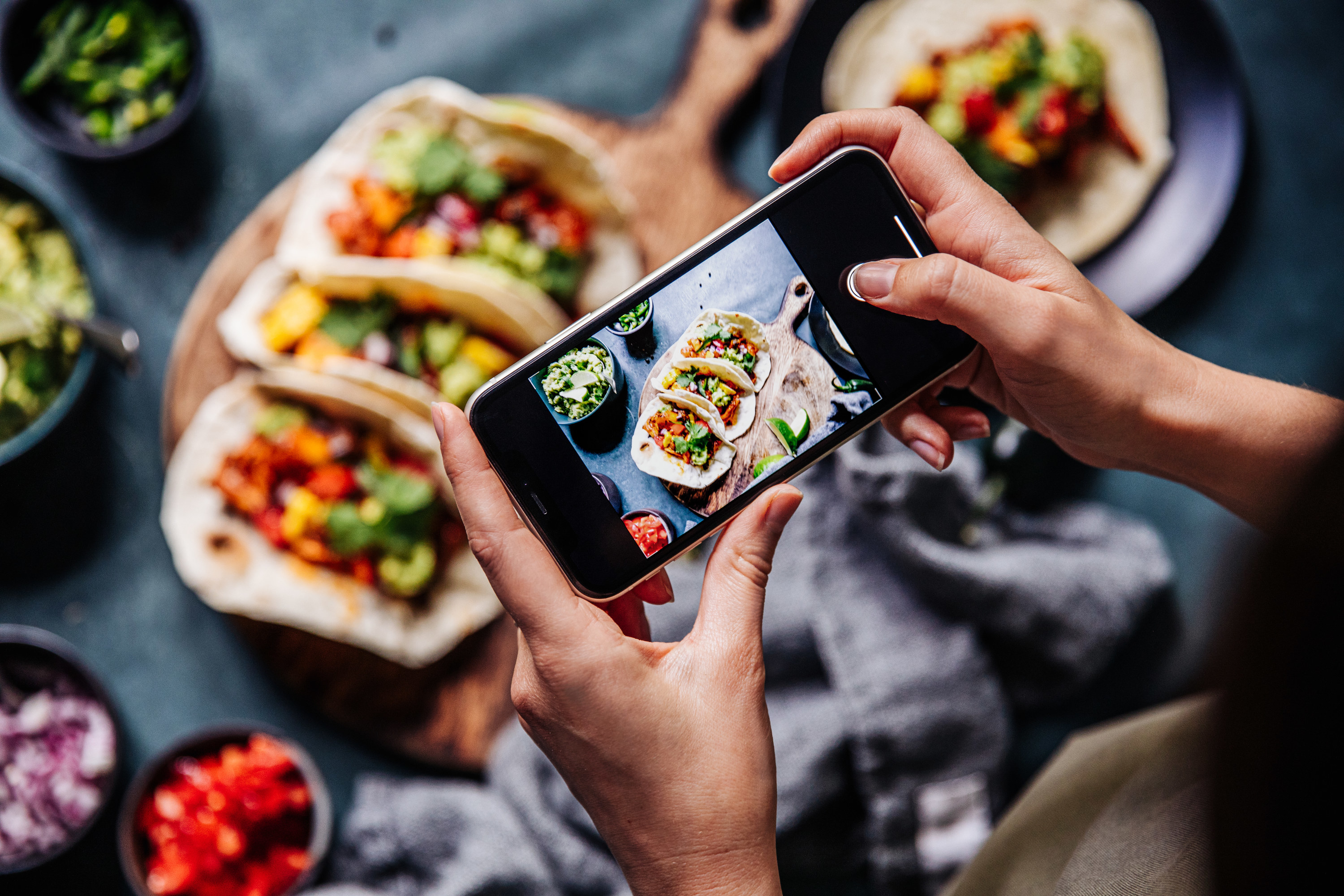photo of a person taking a photo of tacos from their cell phone