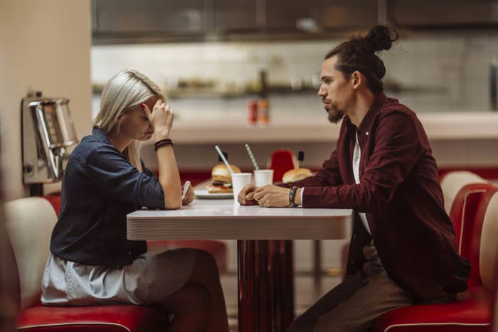 Photo of a guy and a girl looking upset at a diner