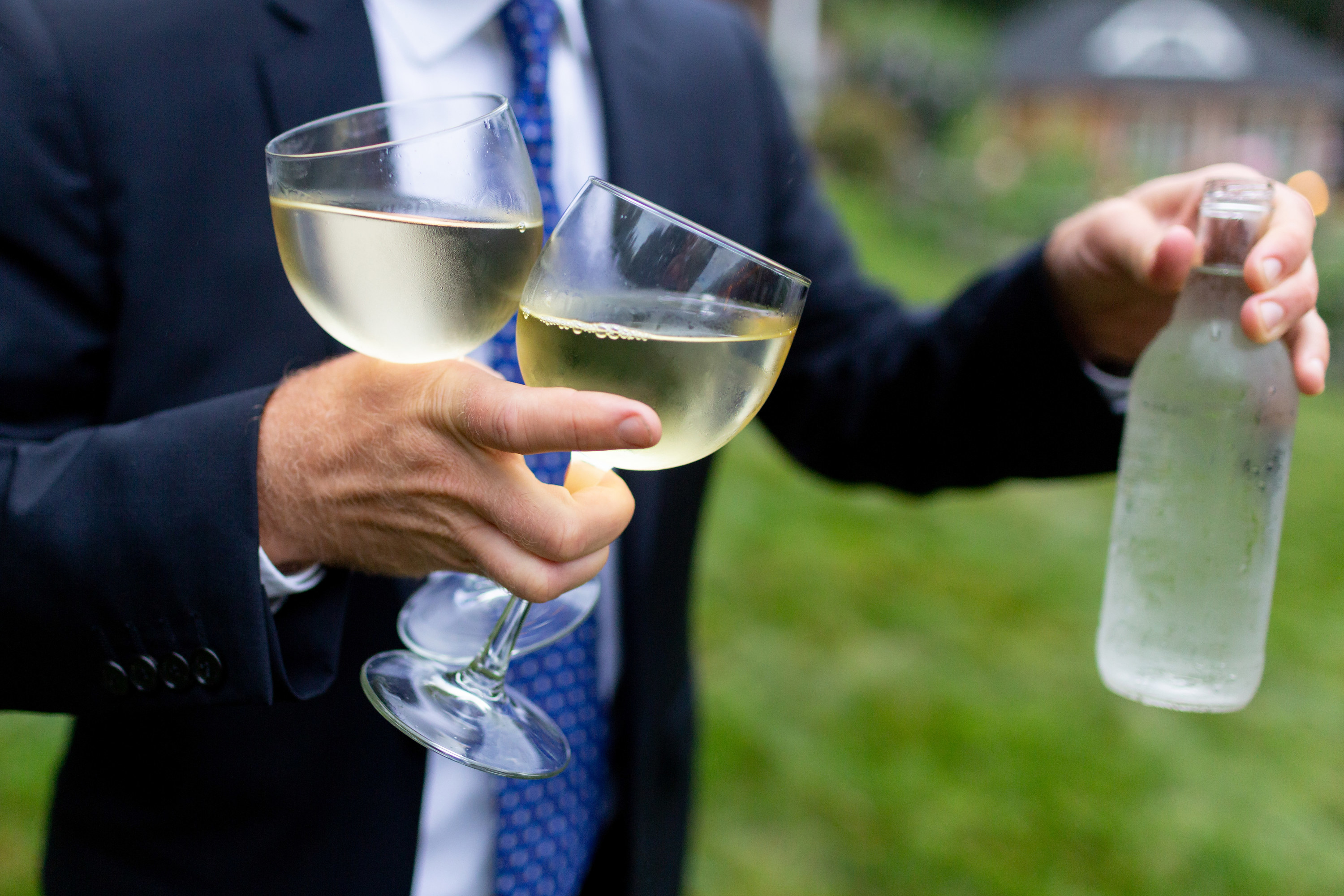Person in a suit holding multiple glasses of wine