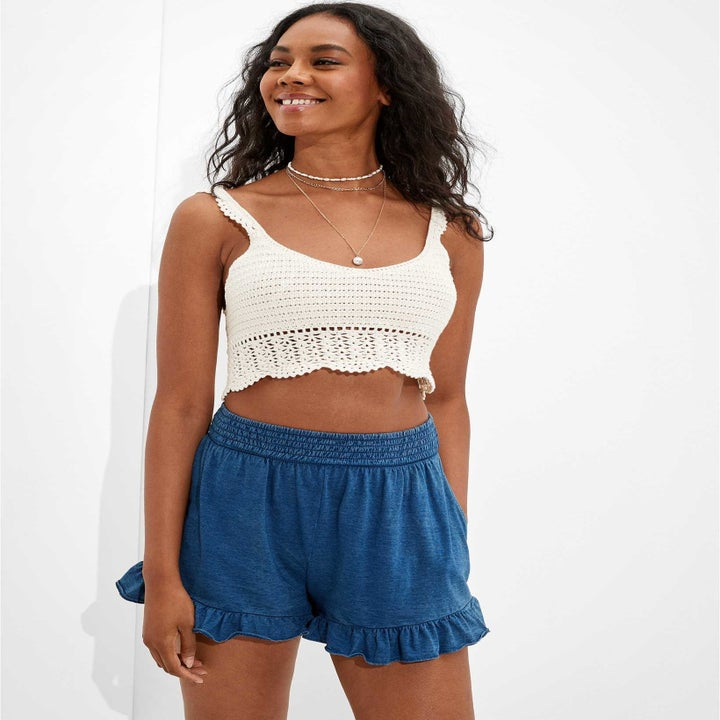 model wearing the ruffle shorts with a white crop top