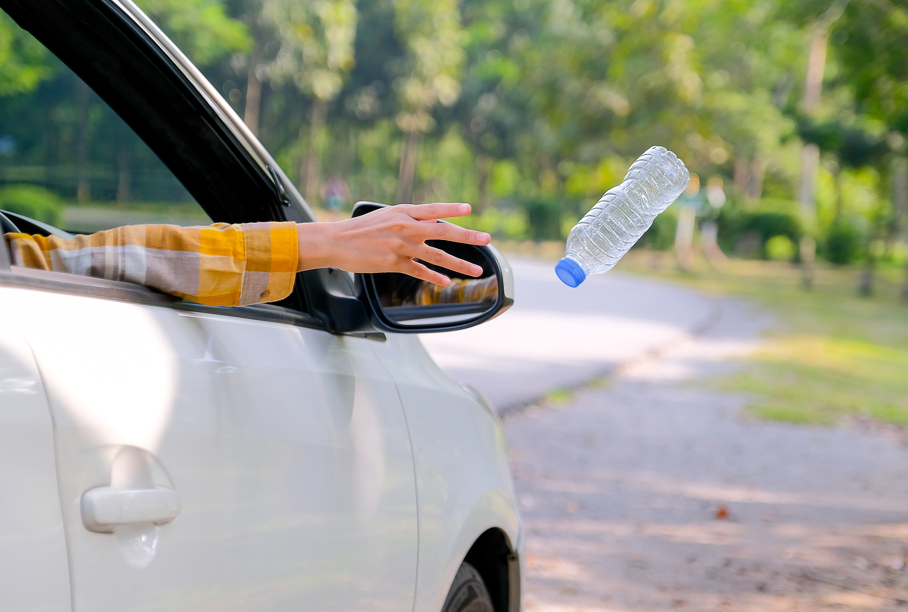Photo of a person tossing a water bottle out the window of their car.