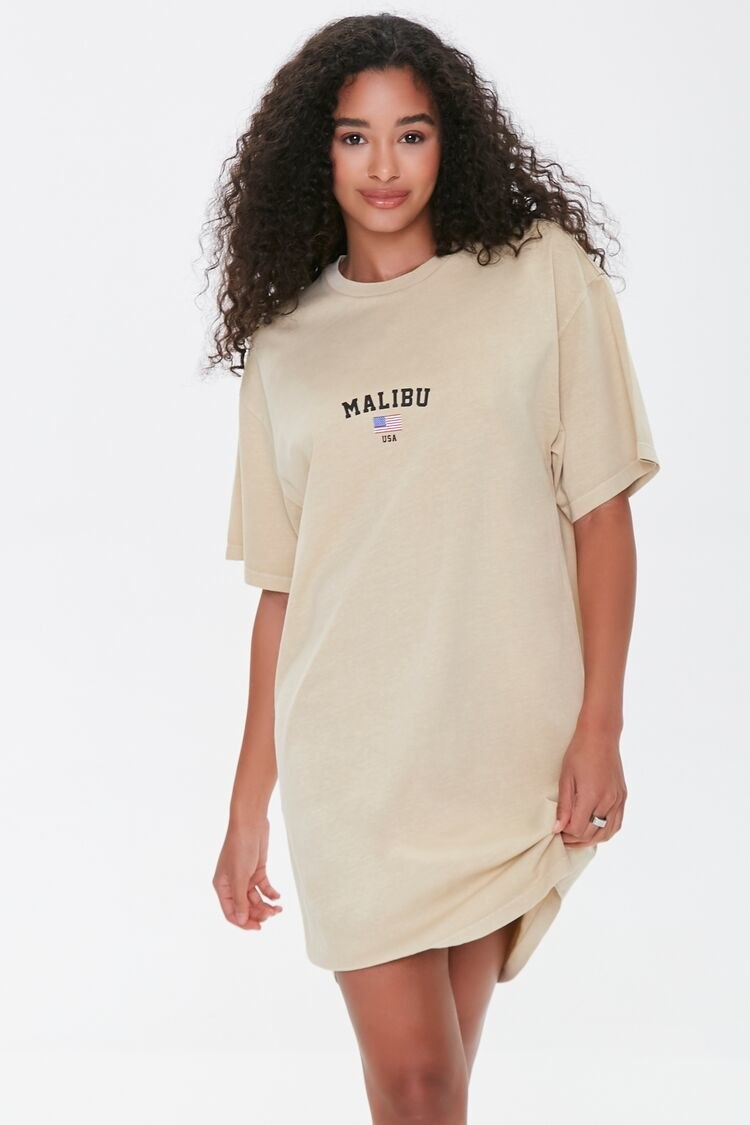 """model wearing the tan T-shirt dress with a """"malibu"""" graphic and small american flag on the front"""