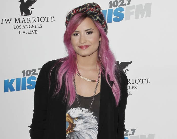 Demi looks casual in a graphic tank and cardigan with pink hair