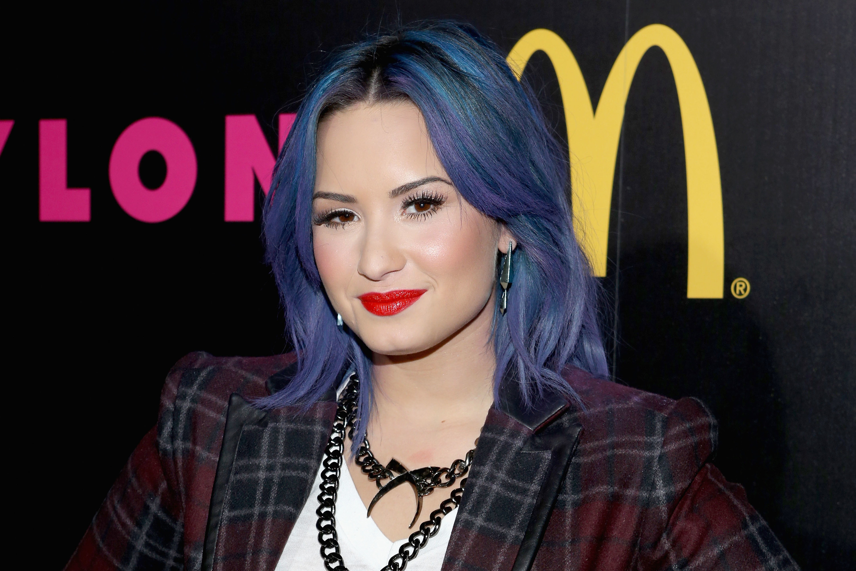Demi smiles with shoulder-length blue hair with highlights in multiple shades of blue