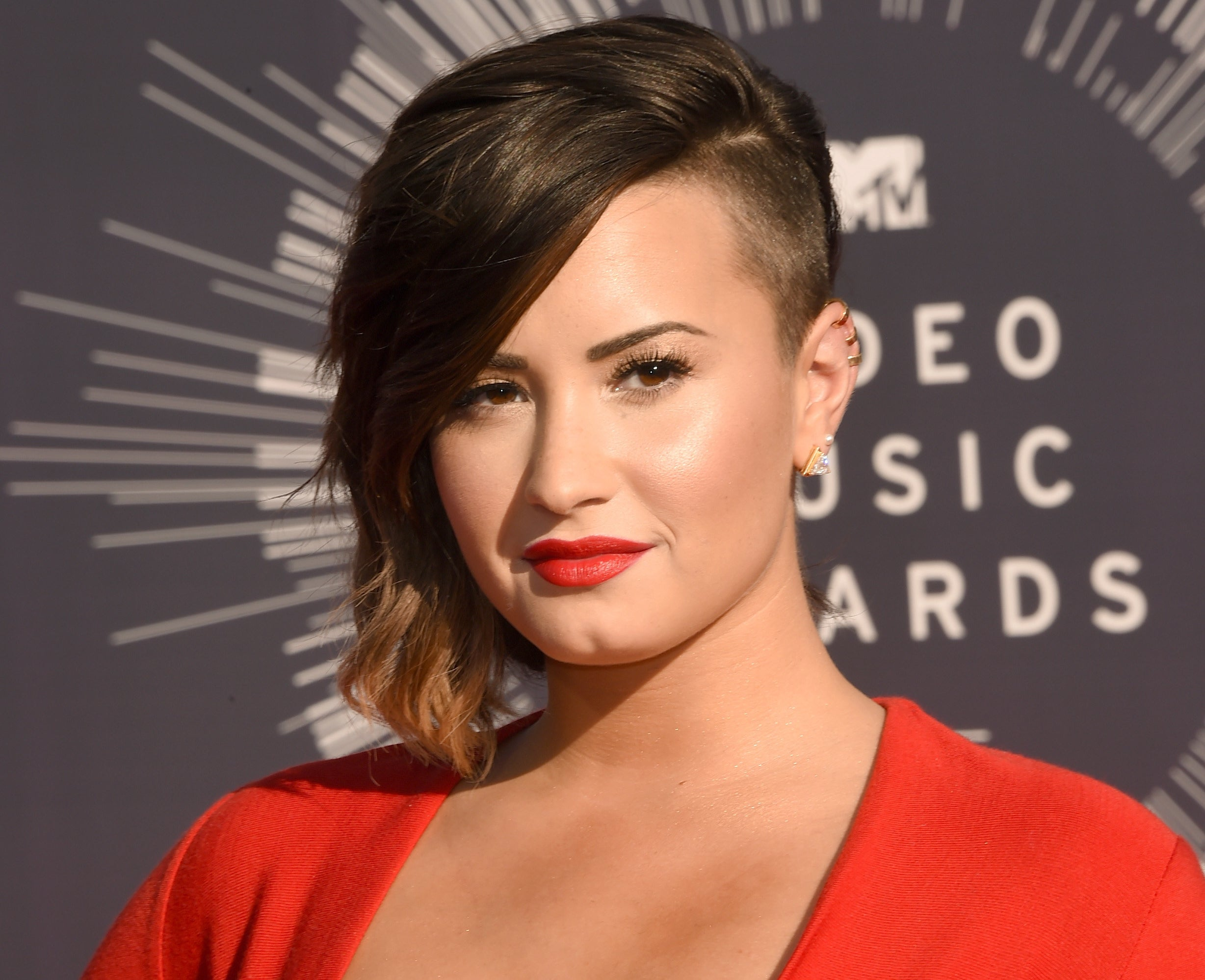 Demi attends an event showing off their shaved side
