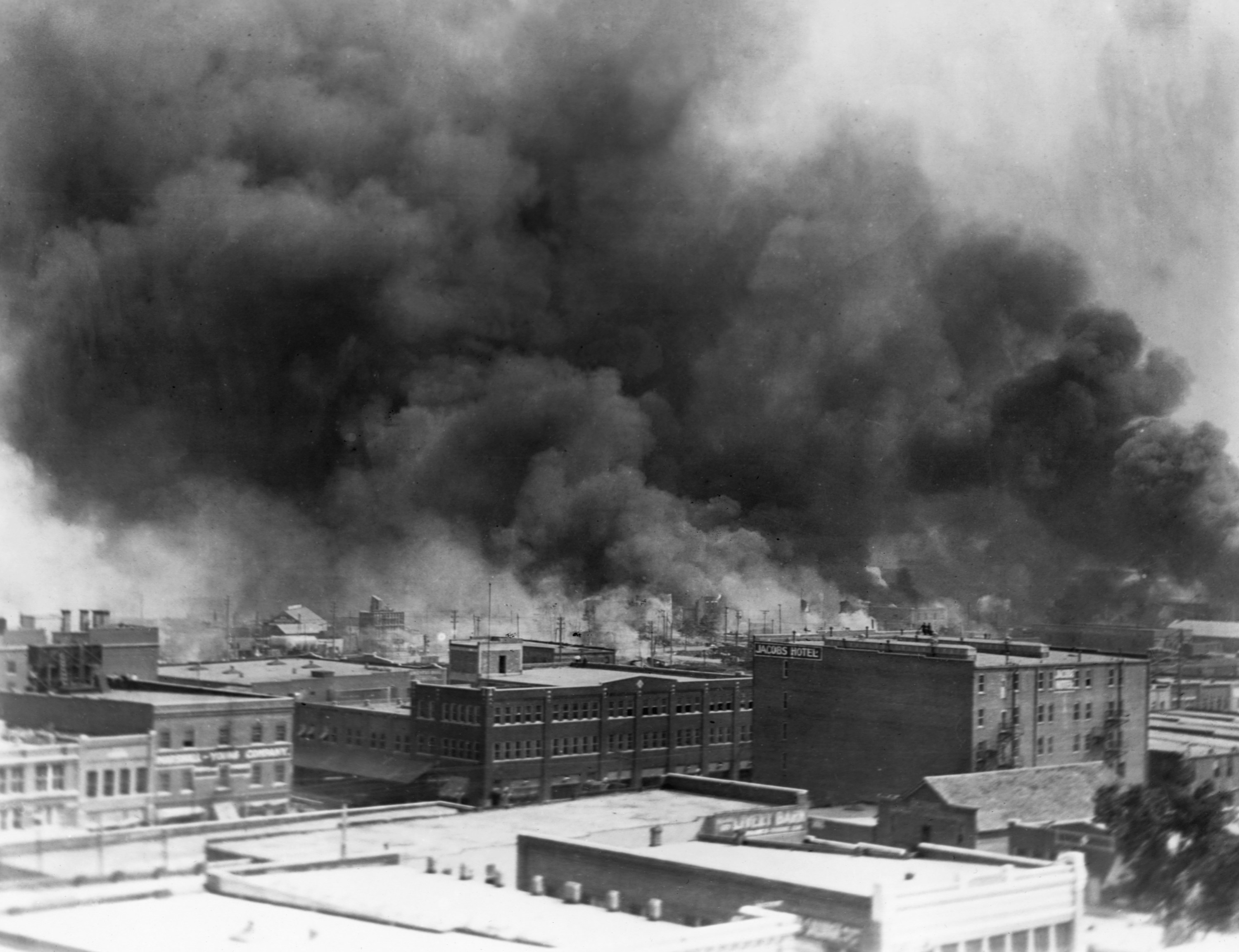 Black smoke billows from fires during the Tulsa massacre in the Greenwood District, June 1921