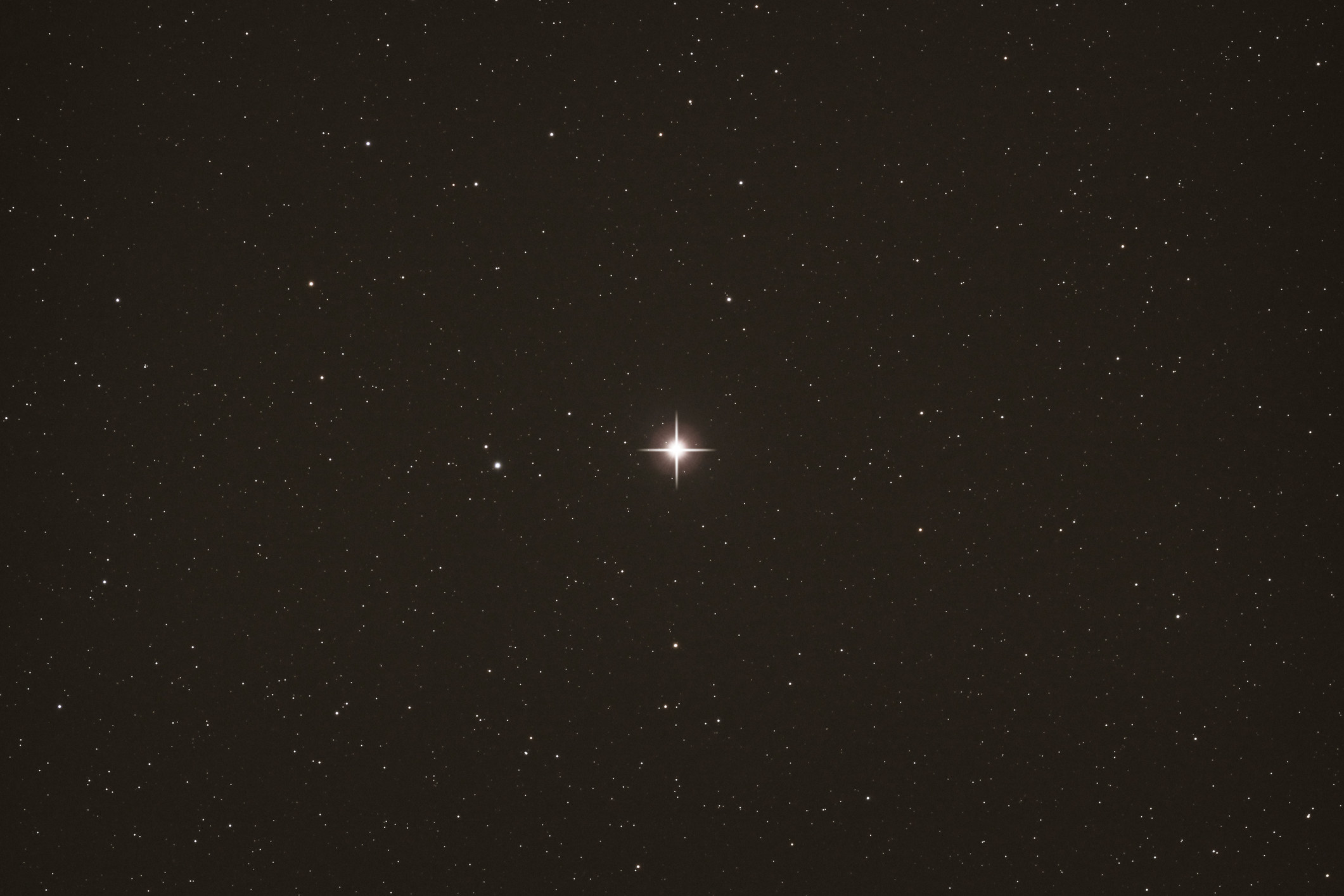A night sky speckled with stars, with polaris in the dead center shining brightest