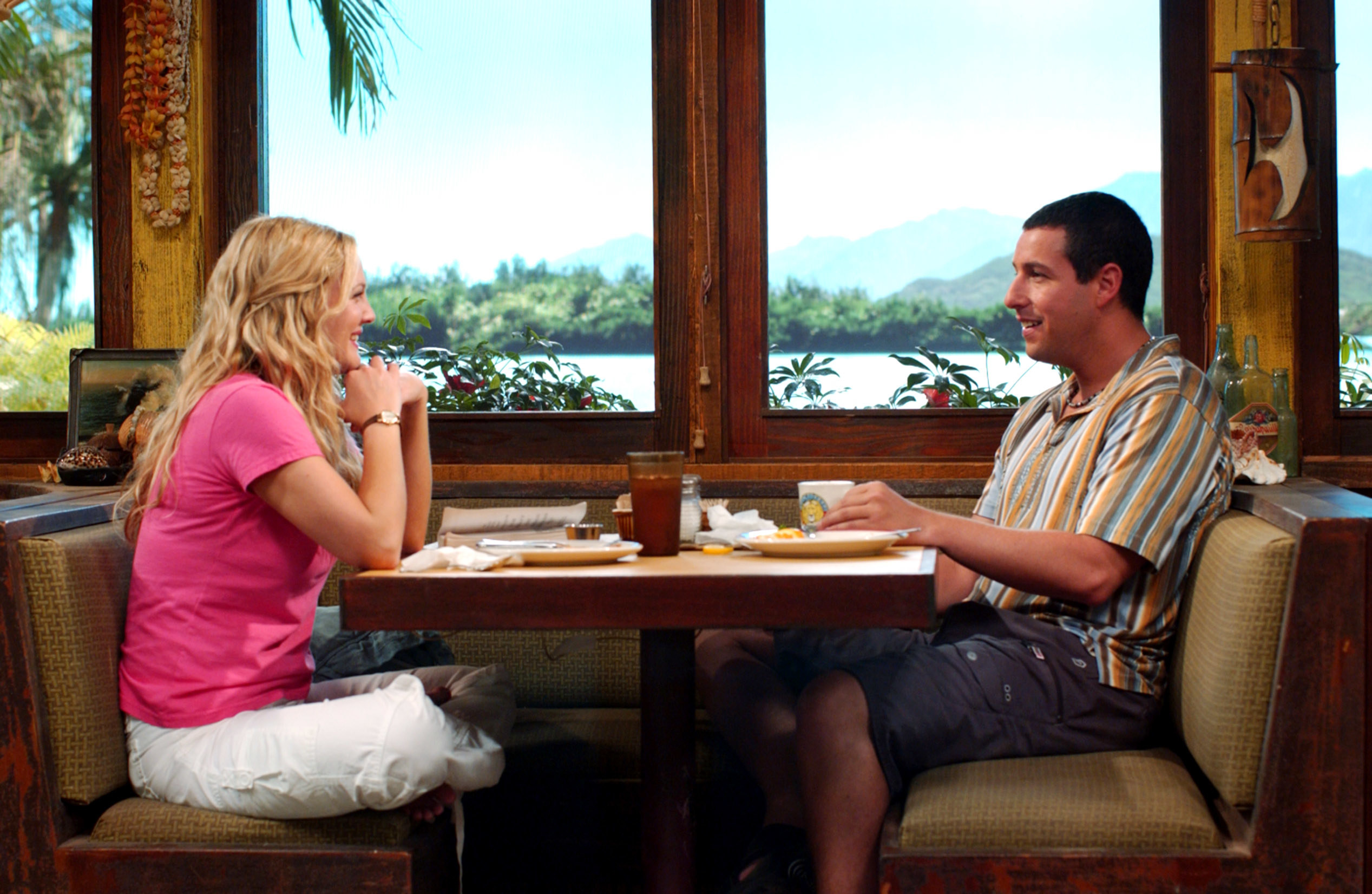 Adam Sandler and Drew Barrymore talking to each other appearing to look happy at a diner