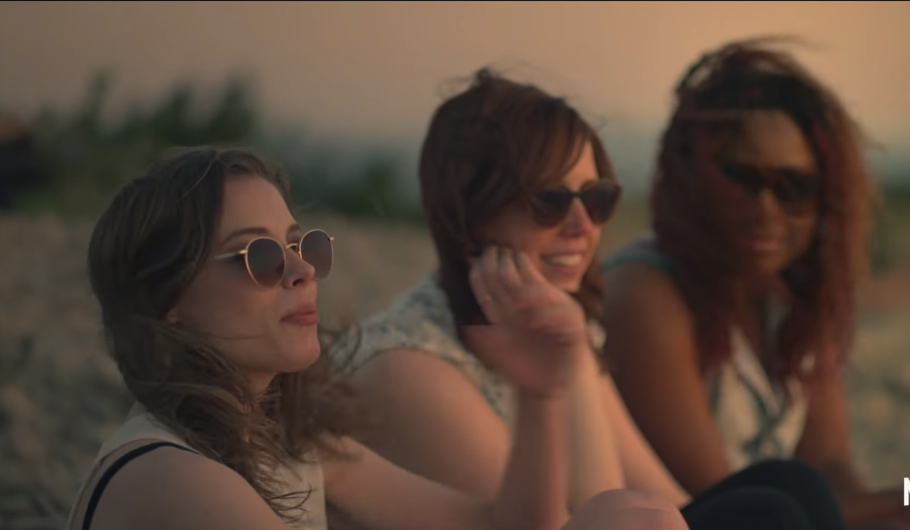 three women sitting on the beach while talking to each other