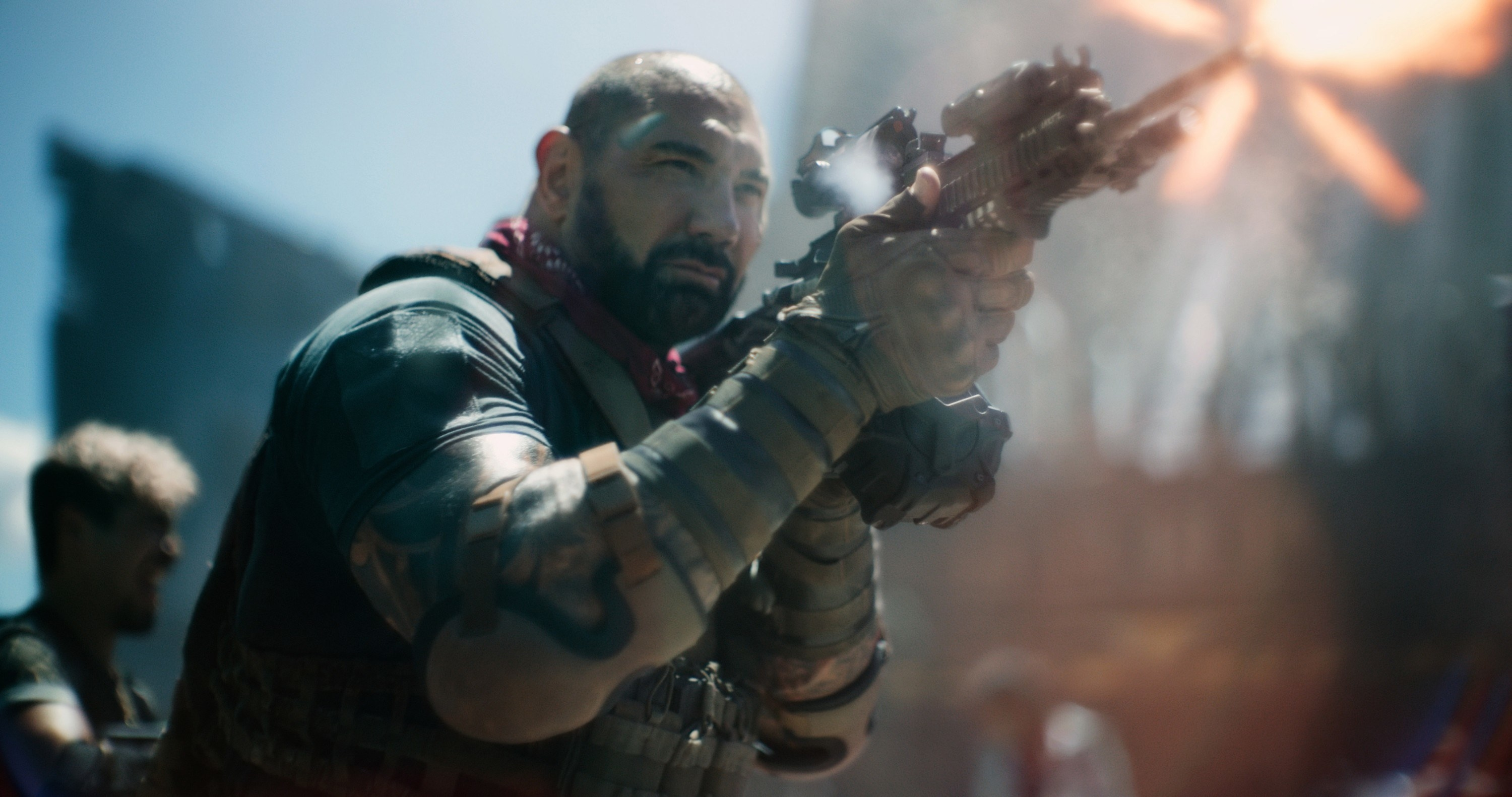 Dave Bautista shooting a gun in a scene from army of the dead
