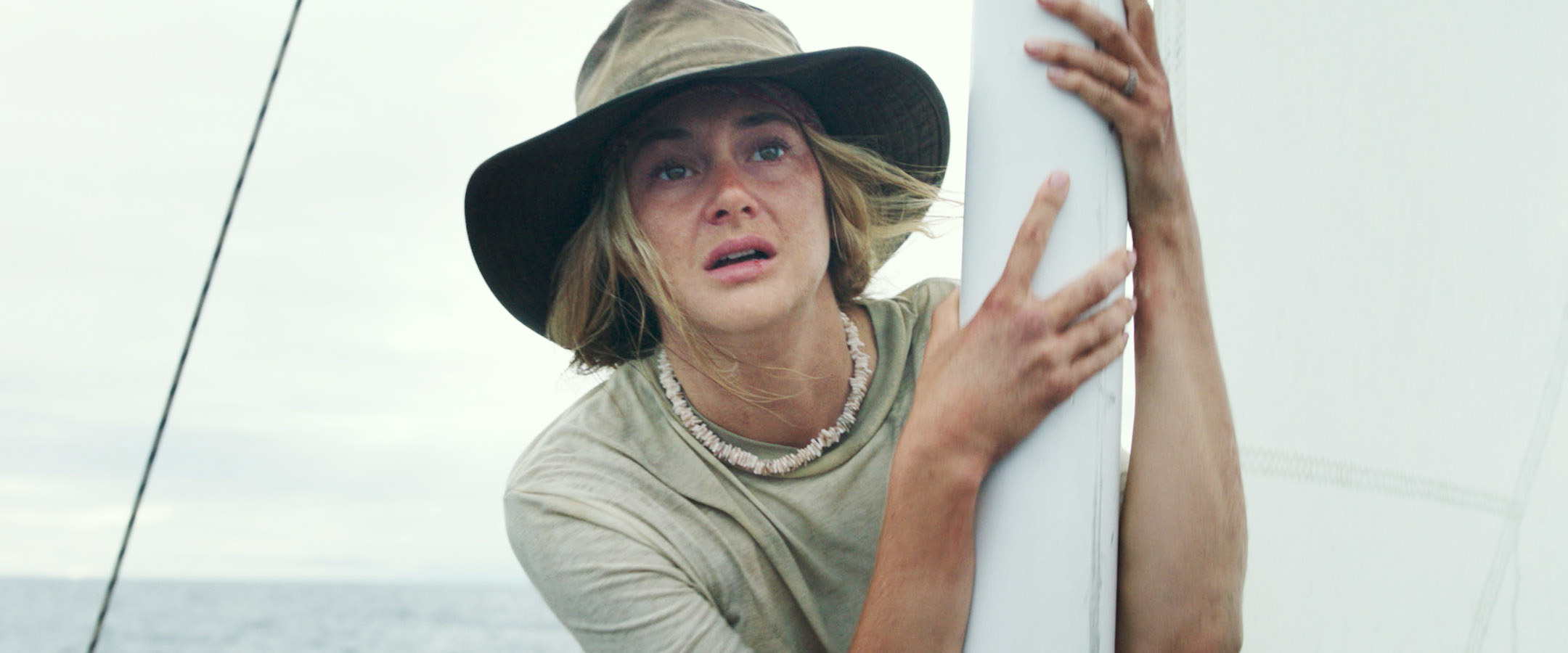 Shailene Woodley holding onto a boat while appearing to look in distress