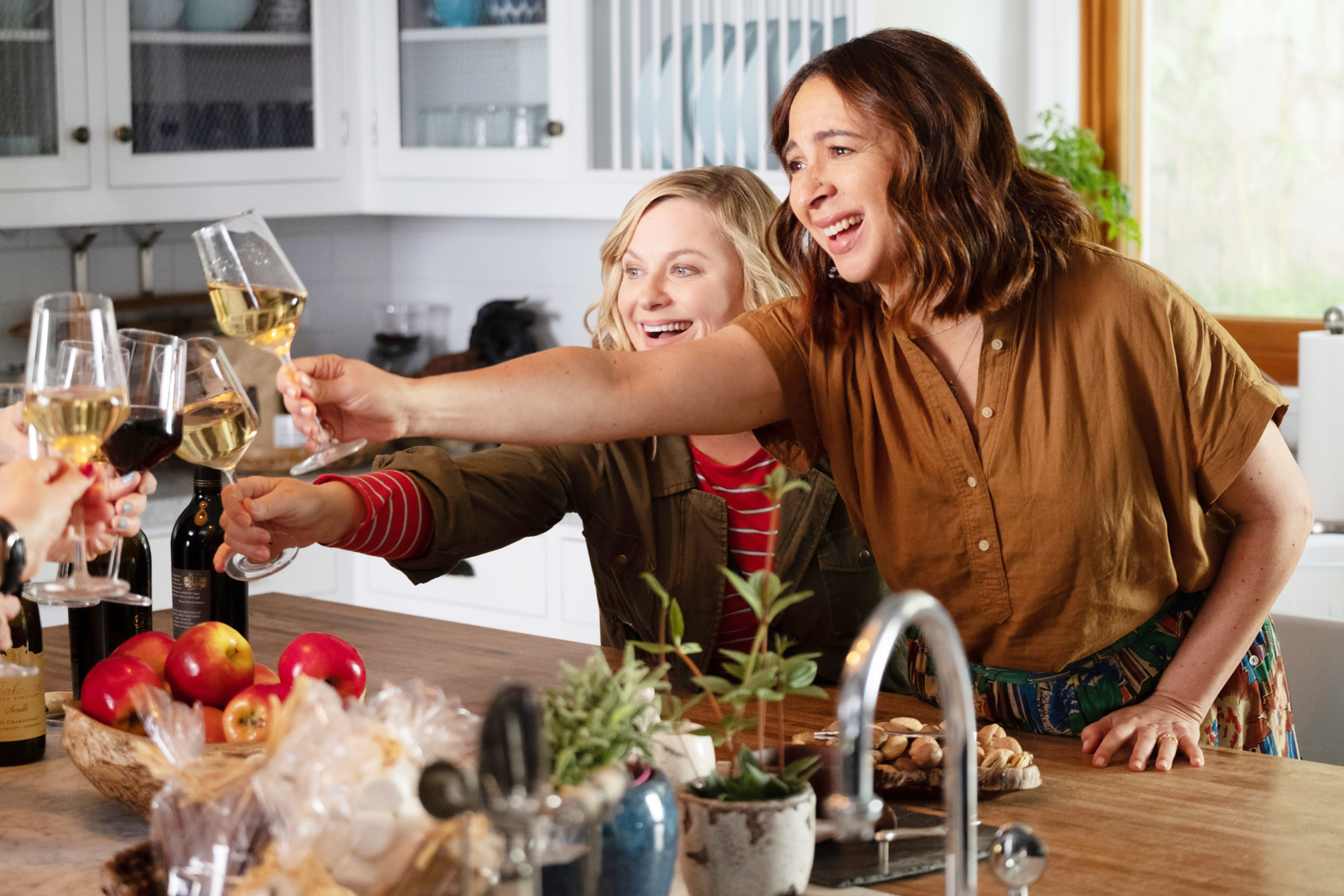 amy poehler and maya rudolph making a toast in the kitchen