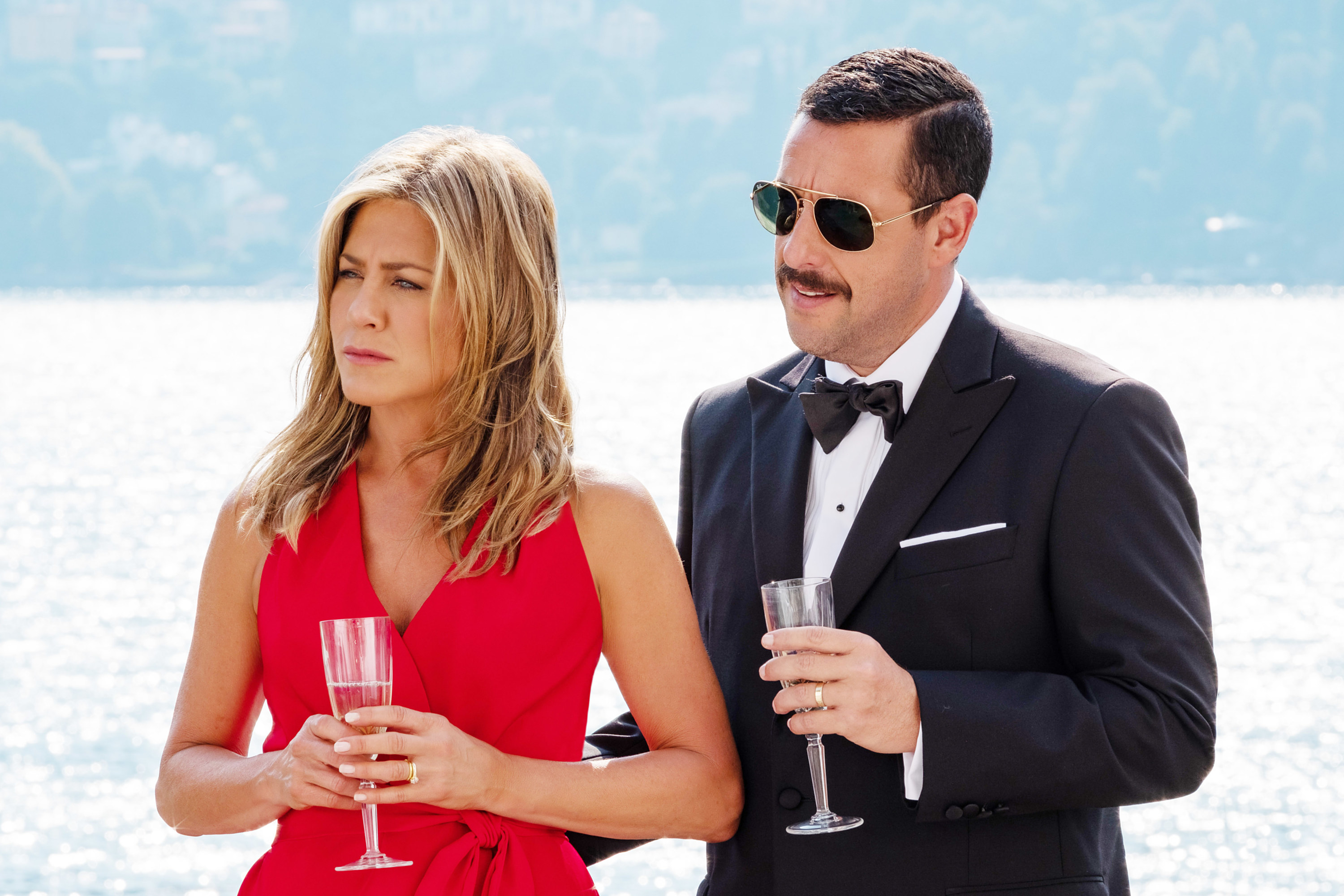 jennifer anniston and adam sandler holding a drink while looking in the same direction in concentration
