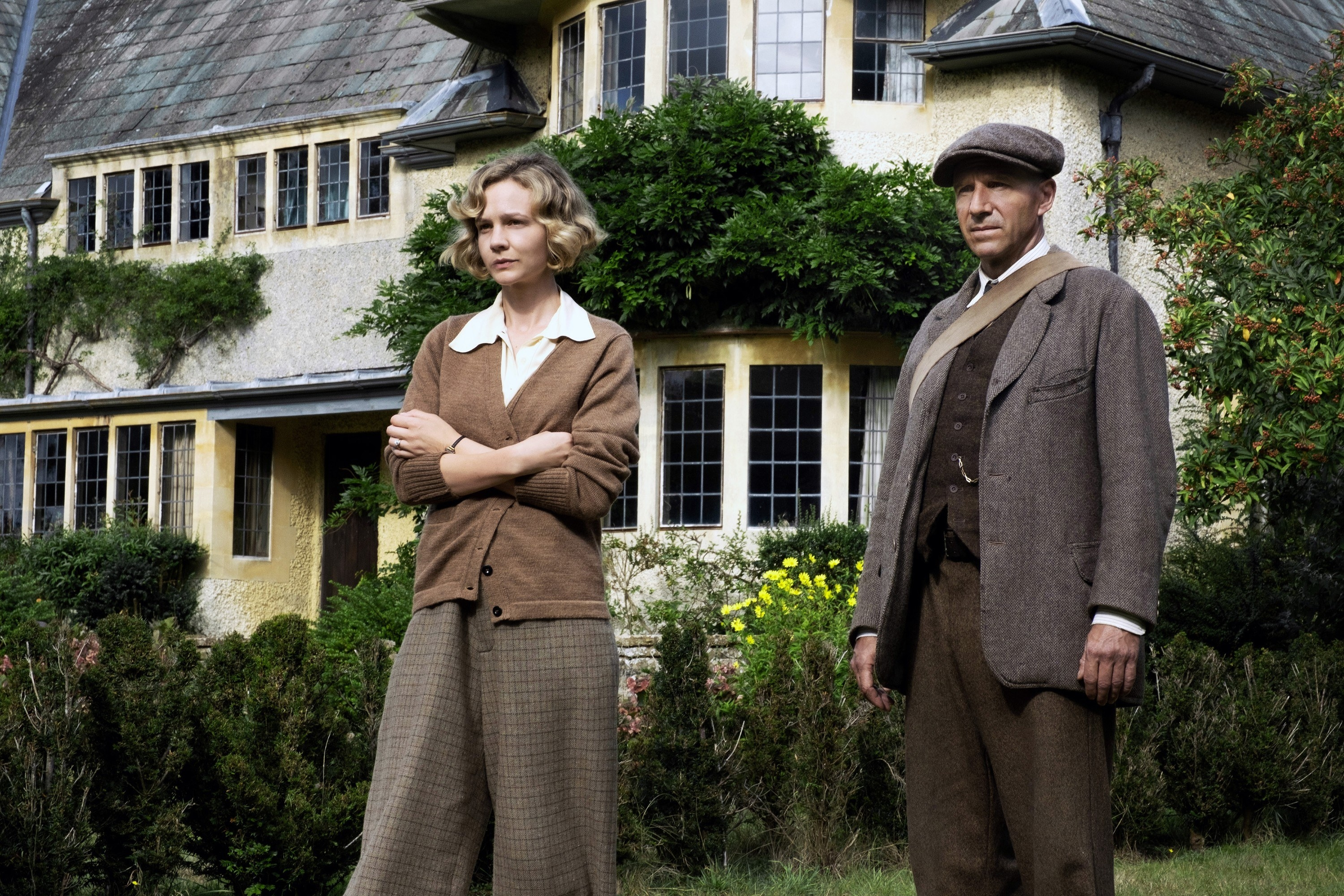 Carey Mulligan and Ralph Fiennes standing outside their house appearing to look serious