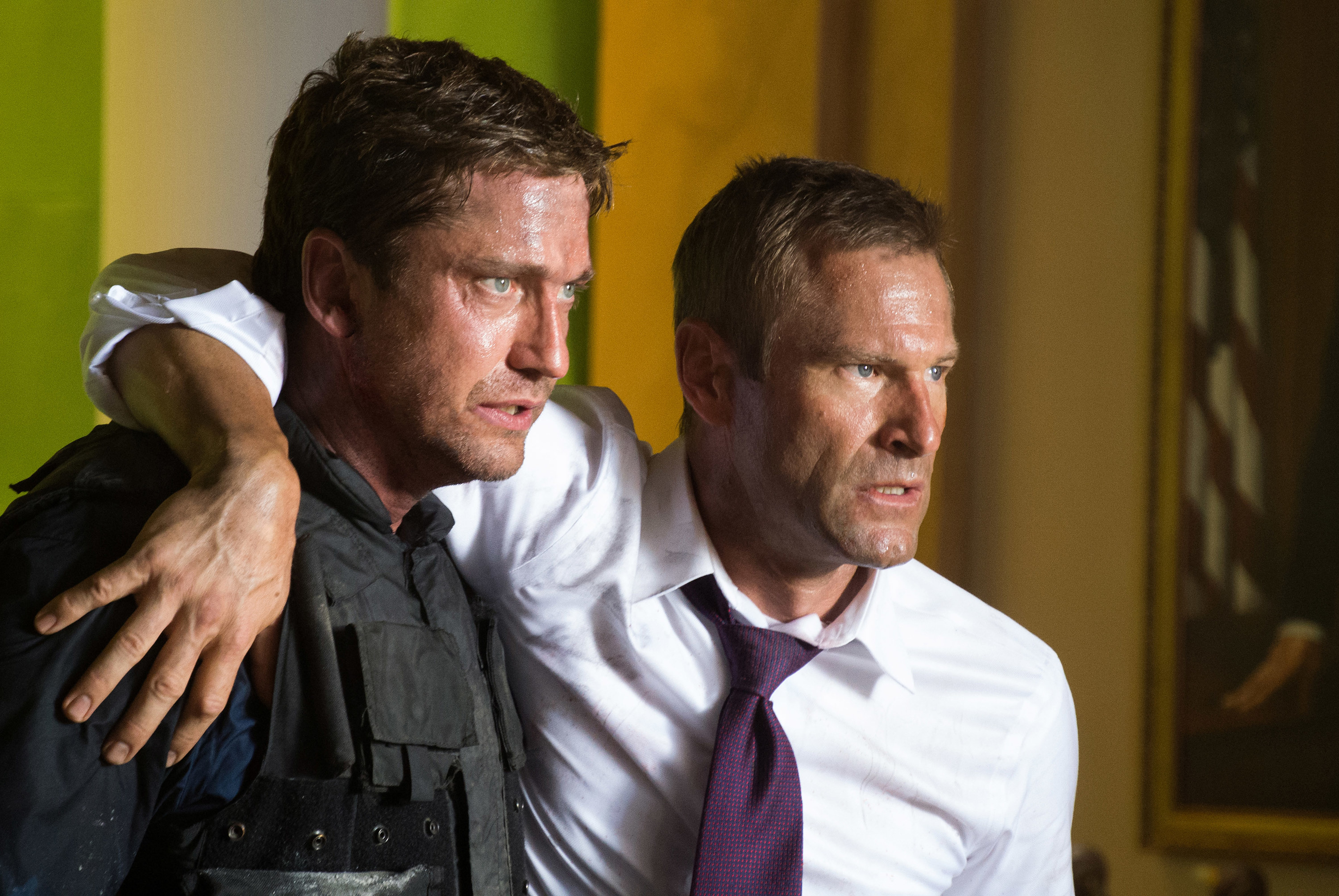 from left Gerard Butler holding Aaron Eckhart while escaping the white house