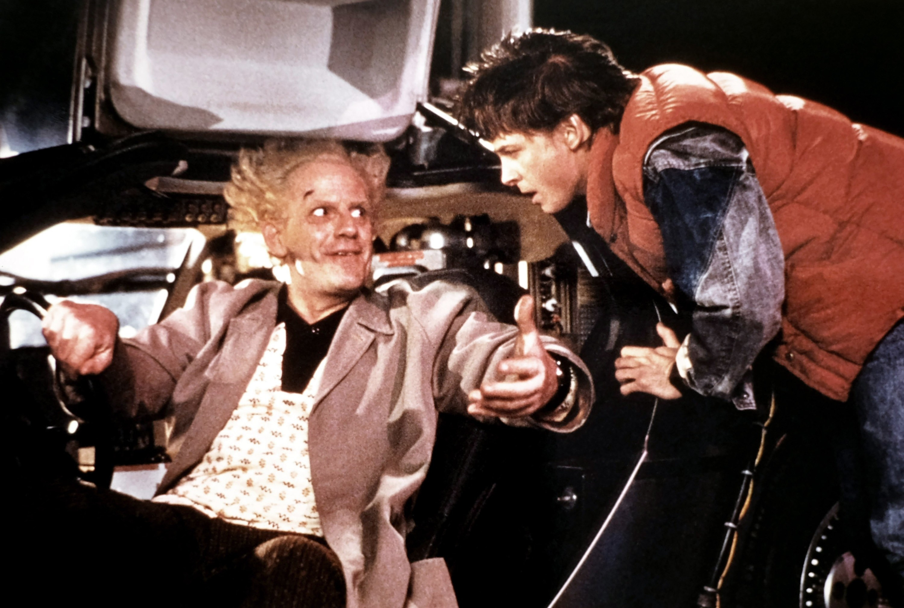 michael j fox and christopher loyd talking to each other while Christopher is in the car in a scene from back to the future