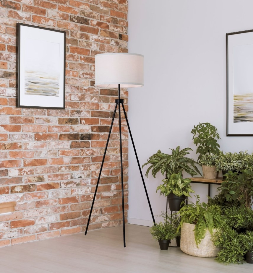 a lamp with tripod black legs and white round shade