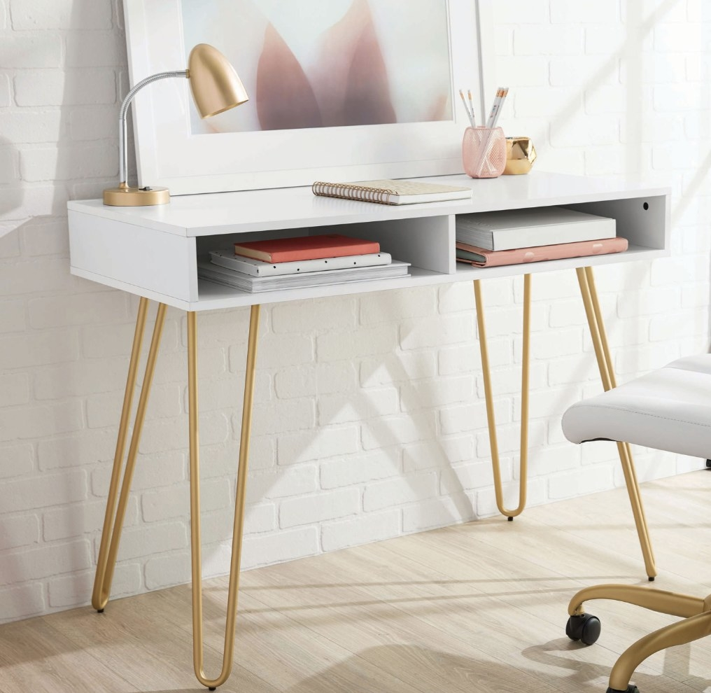 a white desk with storage cubbies and gold hairpin legs