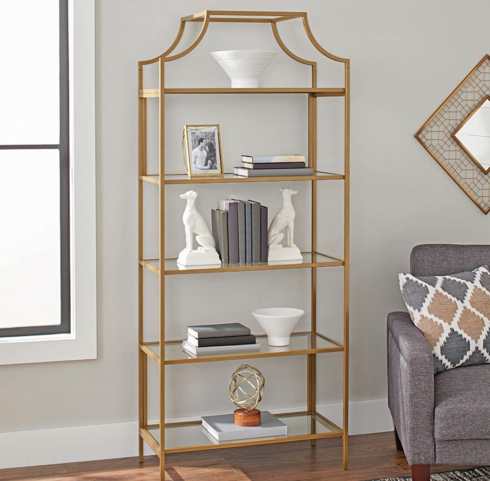 a gold open bookcase with glass shelves