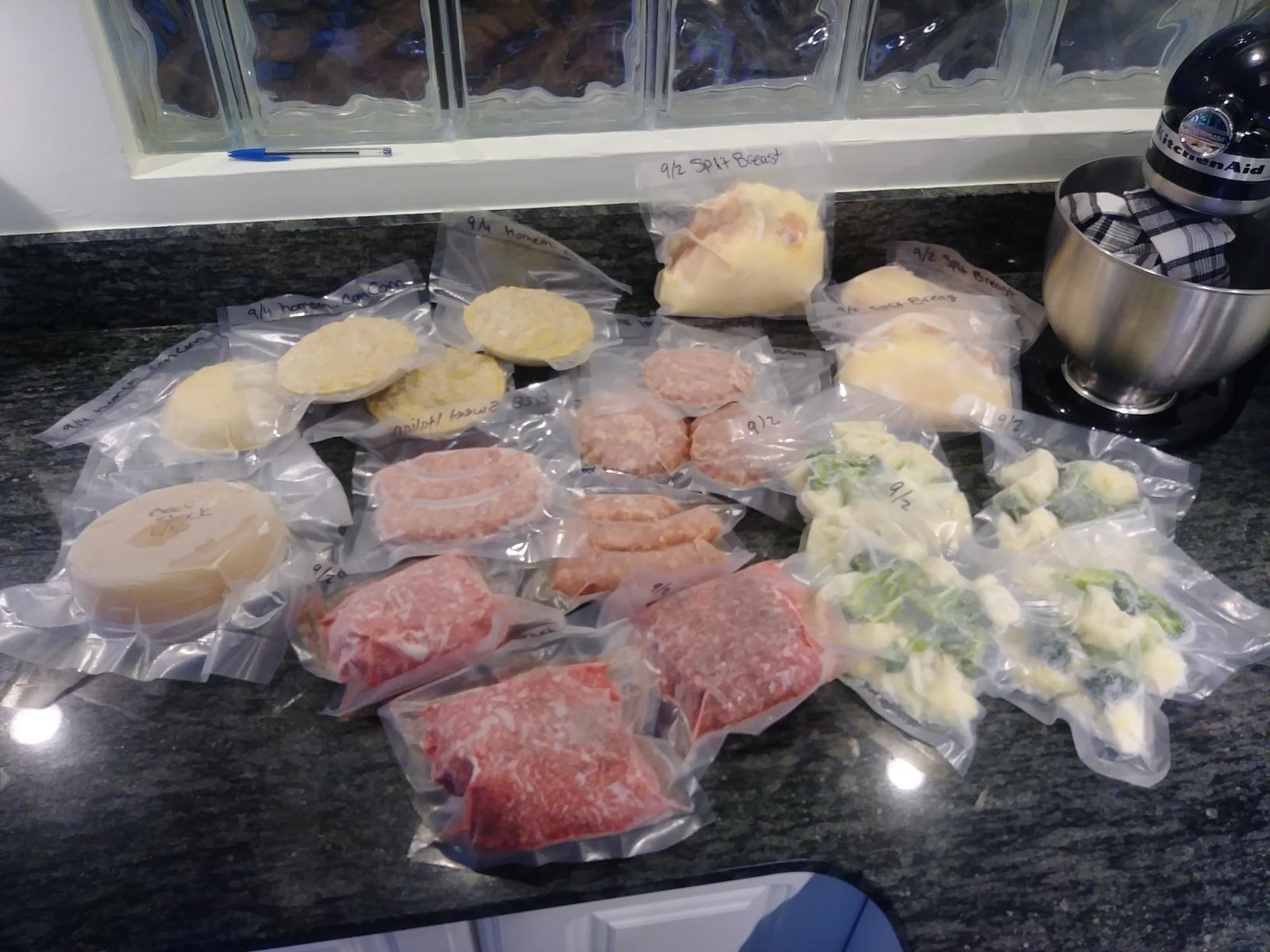 A reviewer photo of a wide variety of foods, sealed in the vacuum bags