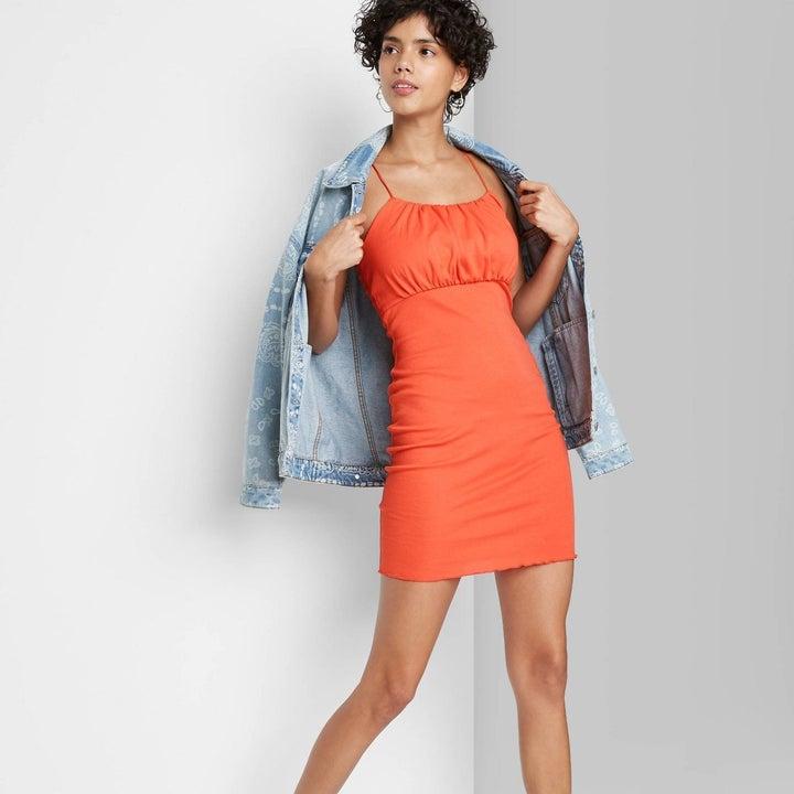 Model wearing orange dress with unfinished hem