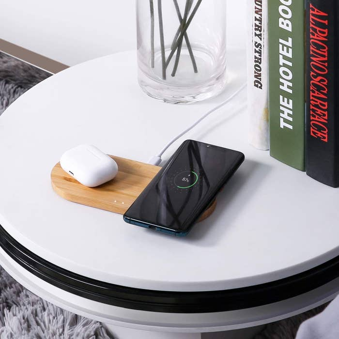 A phone and AirPods on the charging pad