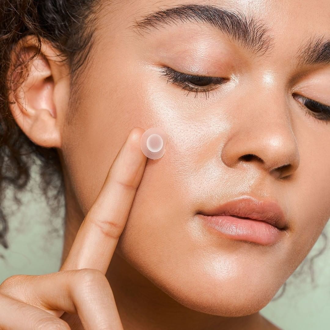 A person placing an acne patch on their face