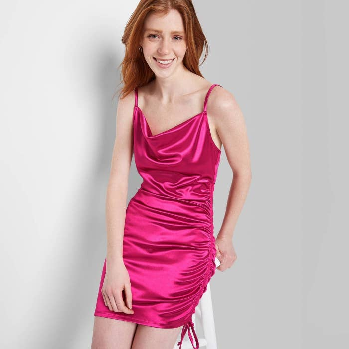 Model wearing sleeveless hot pink mini dress, goes past the thigh area