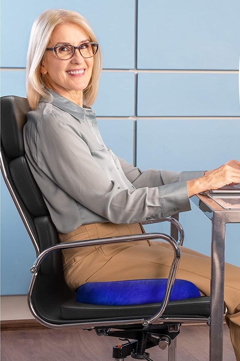 A person sitting on a computer chair in front of their desk with a memory foam cushion underneath them