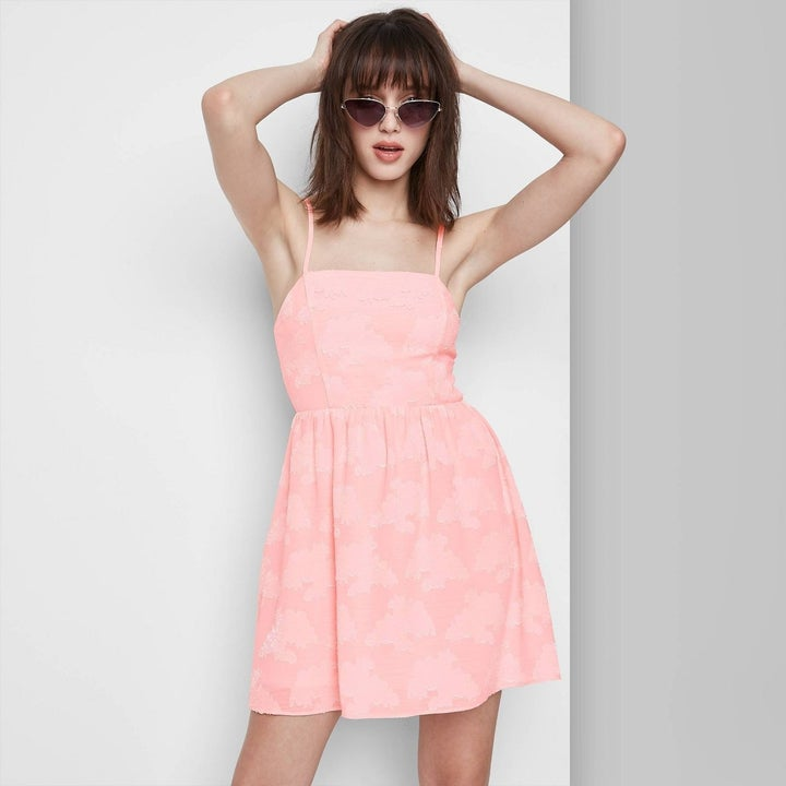 Model wearing pale pink dress, stops above the knee