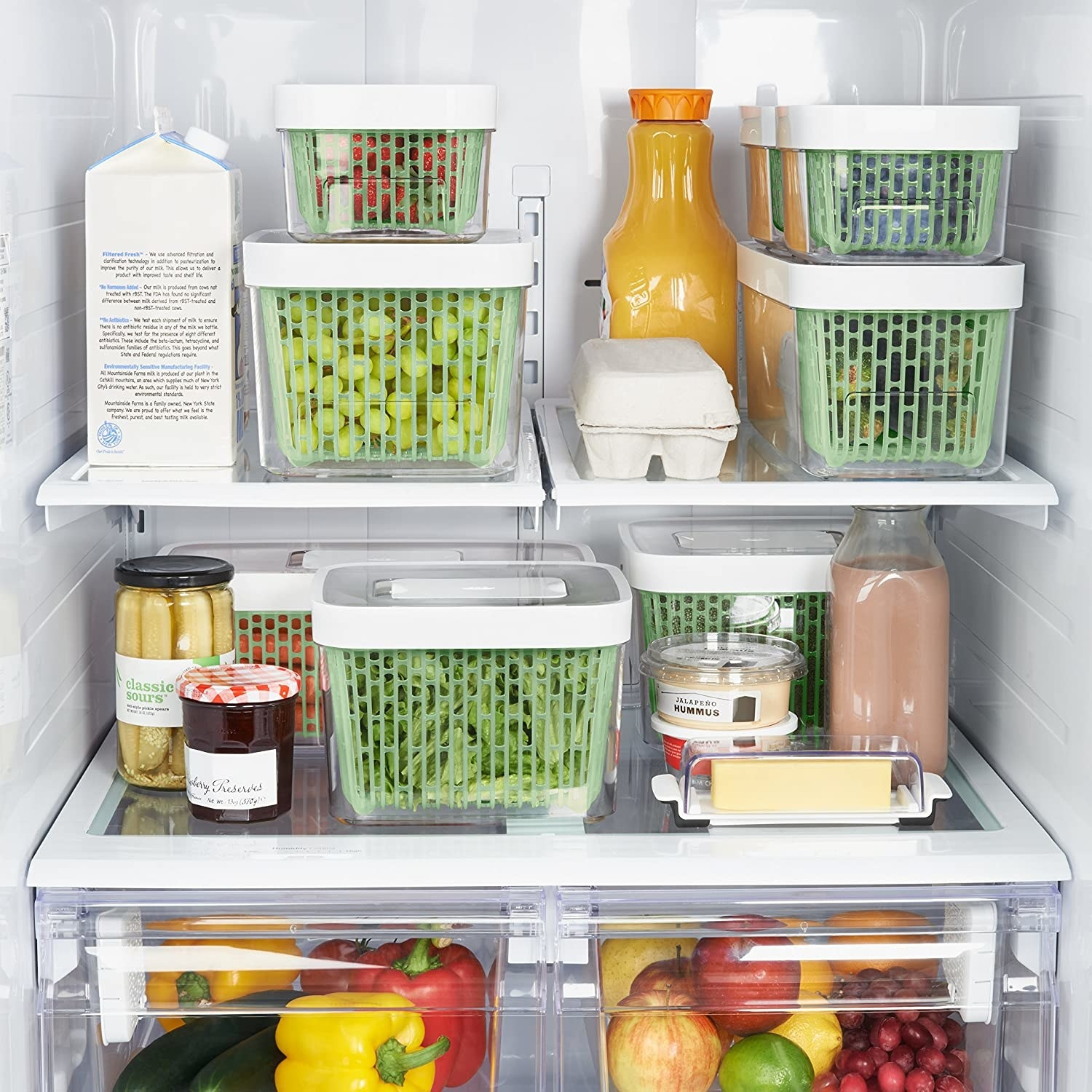An open fridge with several produce savers stacked inside