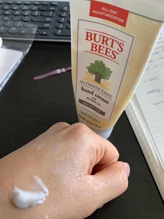 reviewer photo of hand with cream on it next to the product bottle