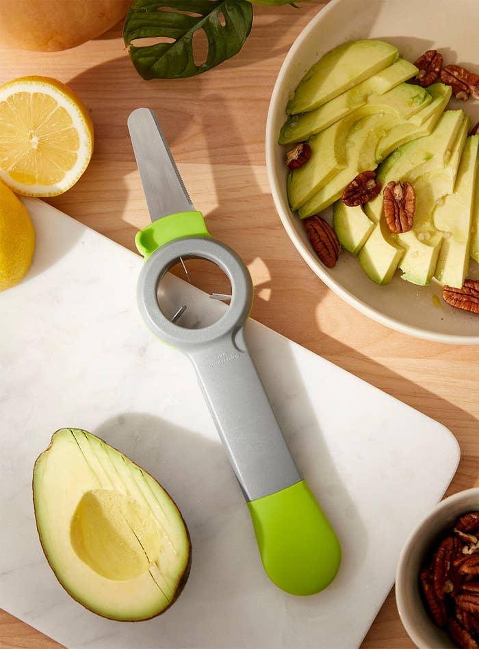 A flatlay of the tool next to a sliced avocado