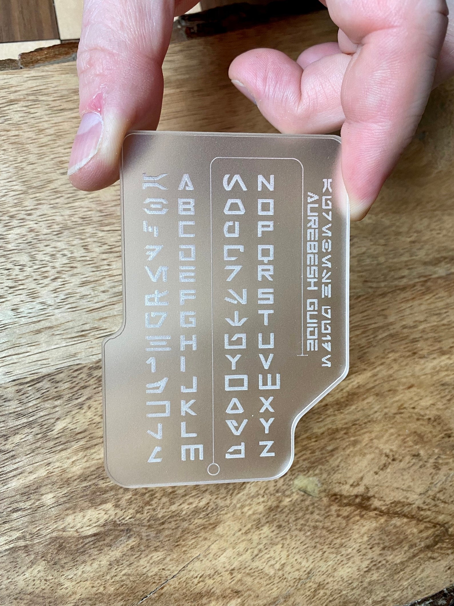 the clear pocket translator with etched letters and symbols on it
