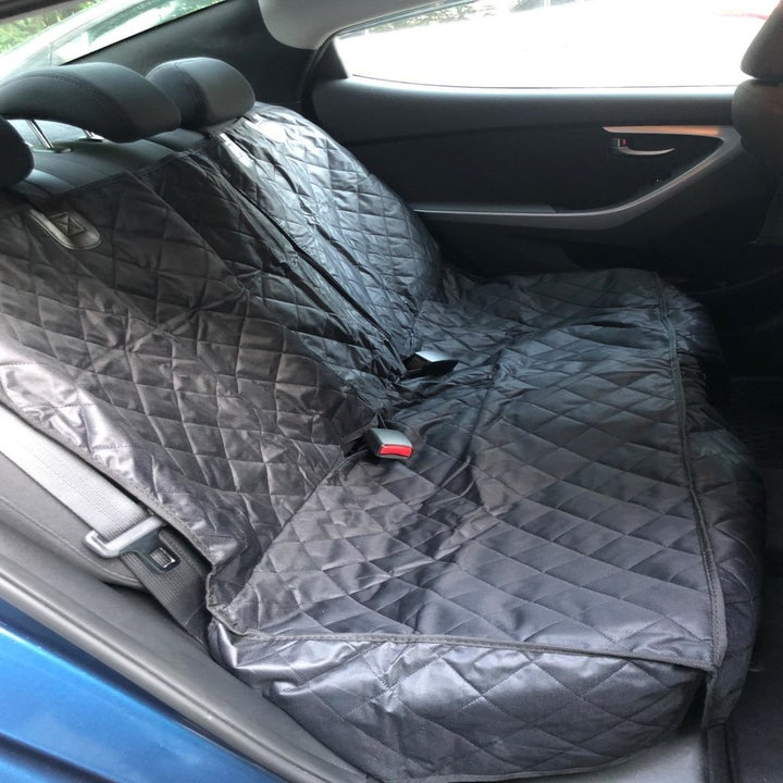 a reviewer photo of the backseat of a car with the quilted cover on it