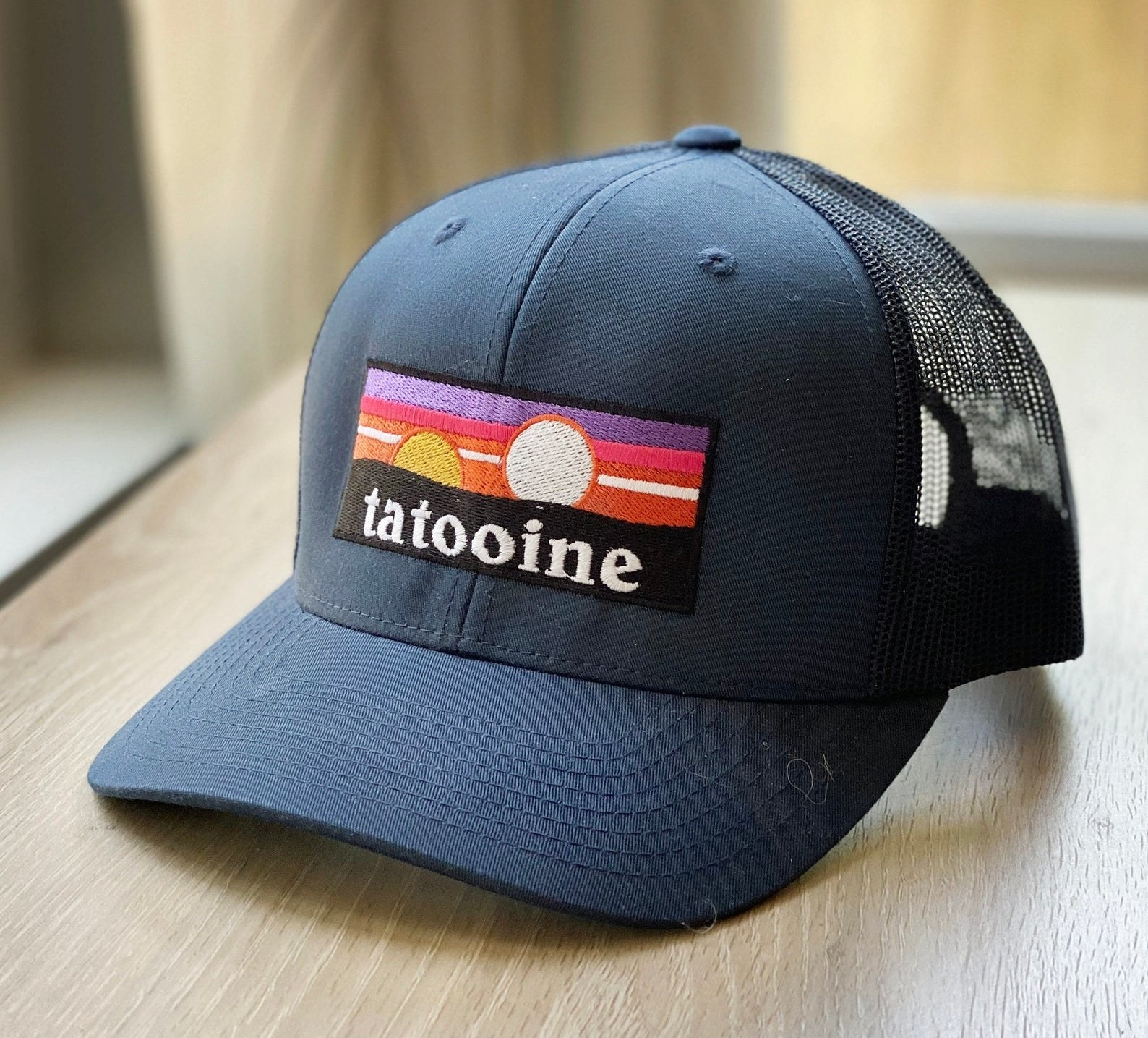 a black trucker hat with a logo of tatooine on it