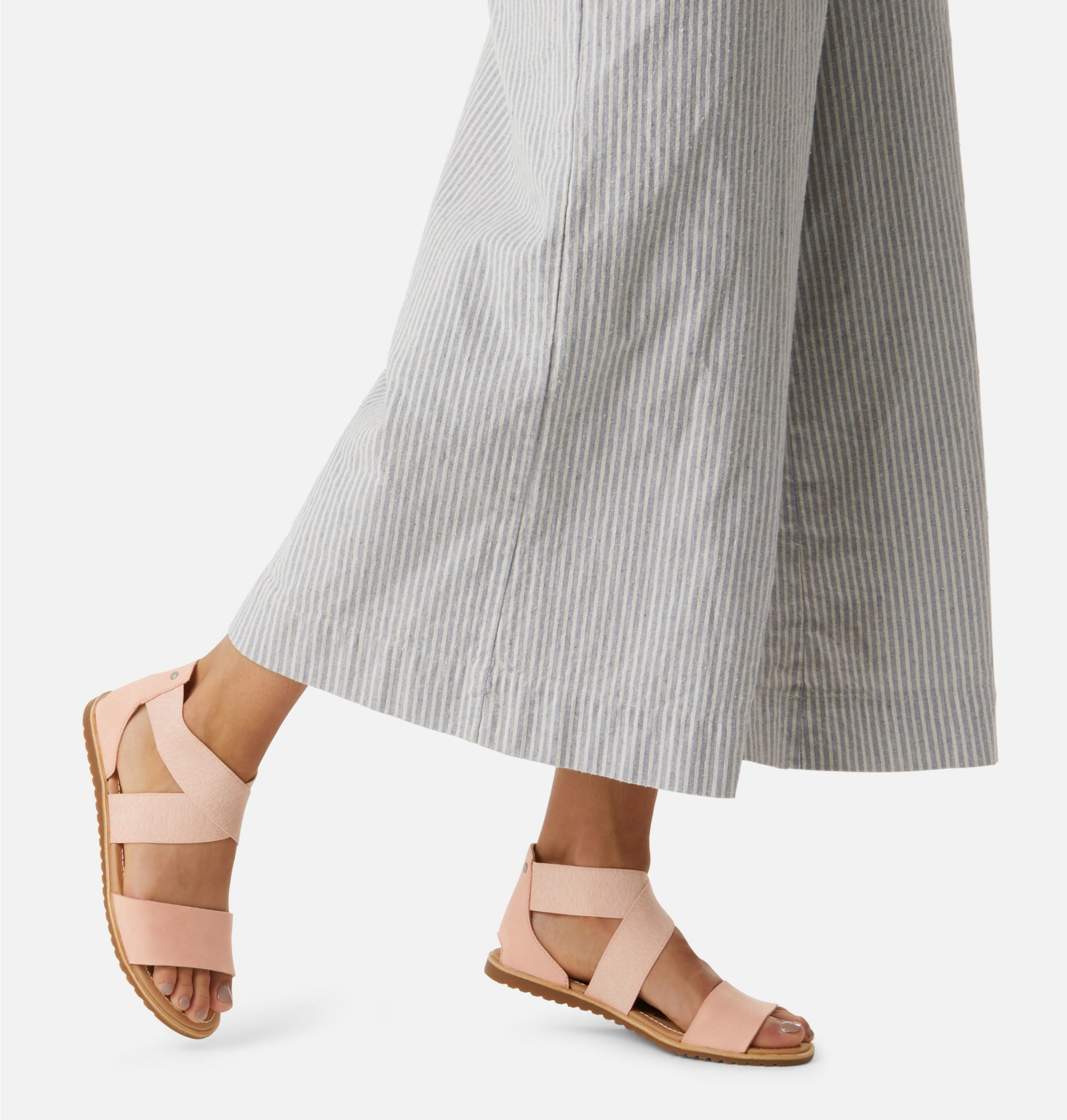 model wearing flat wide-strap peach sandals with heeled back and criss-cross ankle