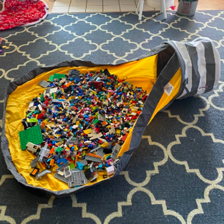 The bag undone with thousands of small toy pieces out on the attached play mat